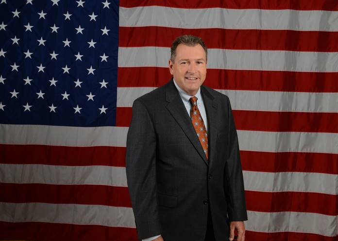 man in suit in front of flag