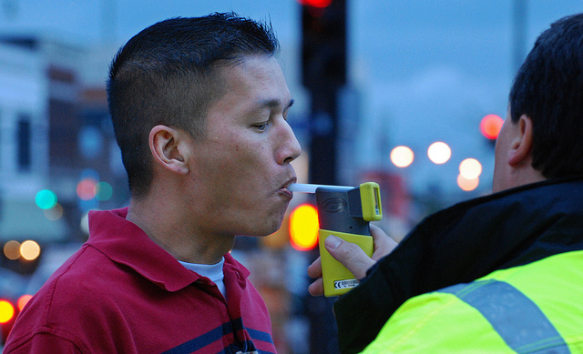 DUI laws in Arizona - person blowing on a breathalyser
