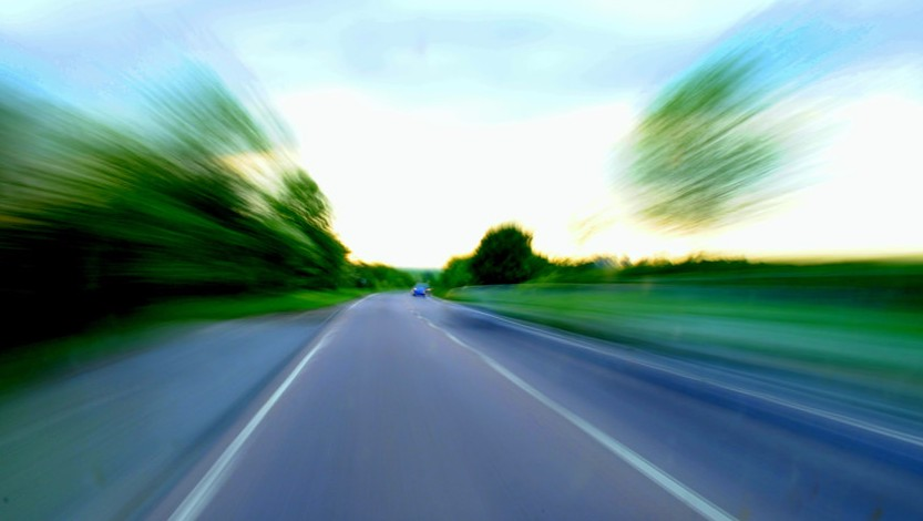Speeding, traffic, law - blurred image of a car on a paved road