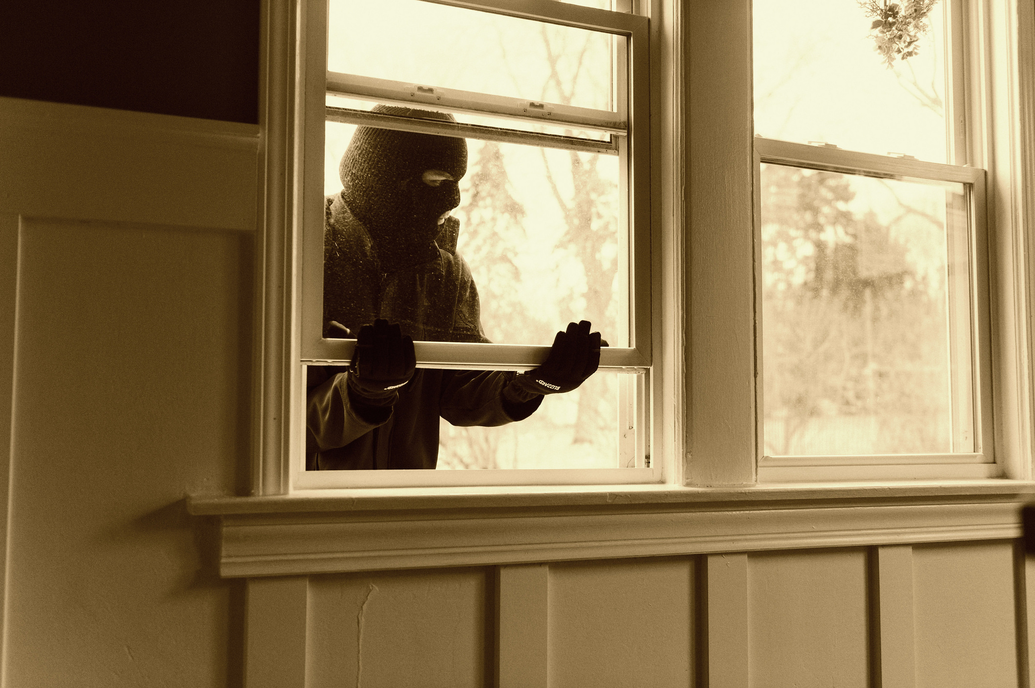 masked man opening the window of the house