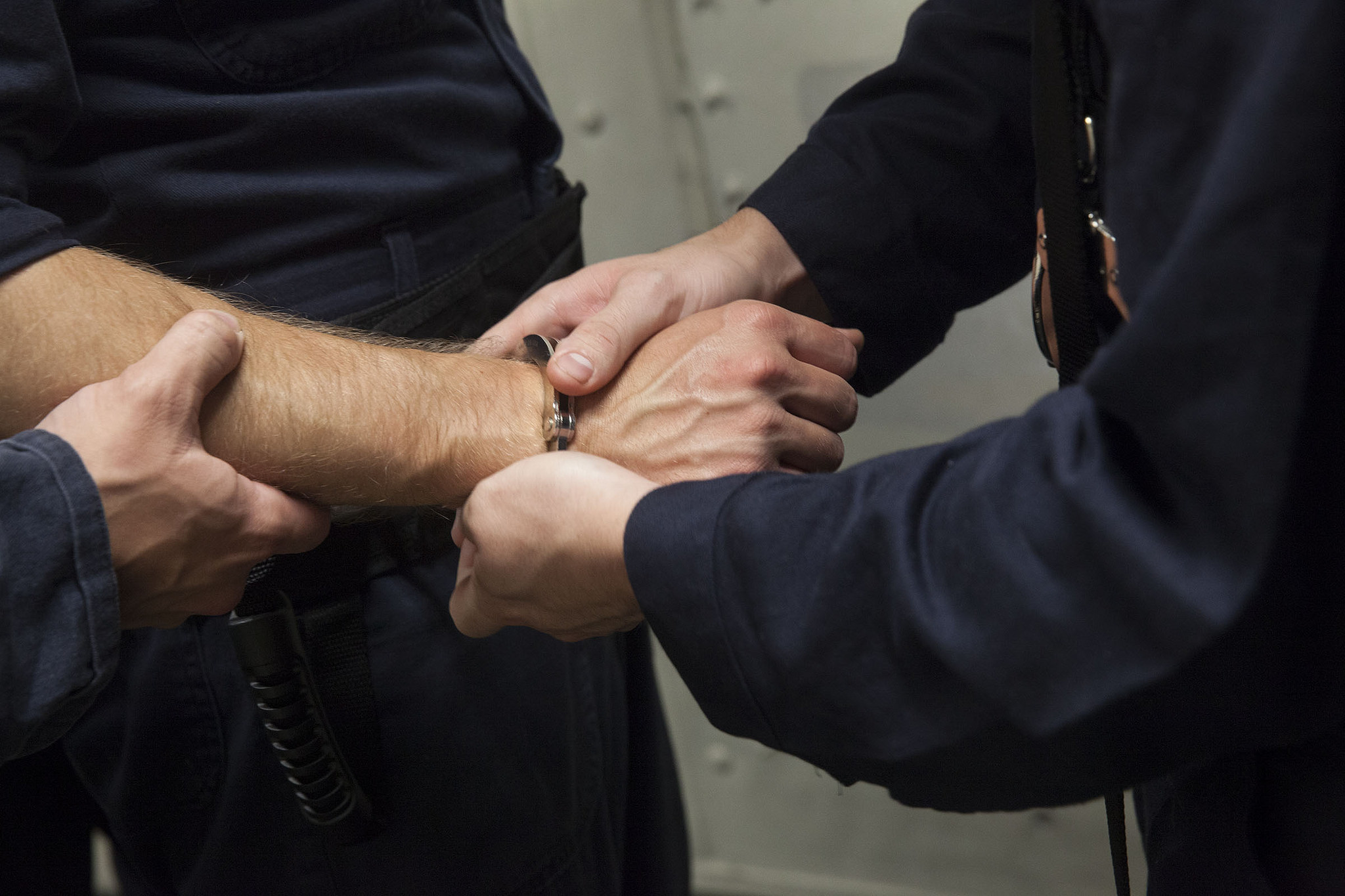 certified criminal law specialist in Phoenix, Arizona - officers restraining a person with handcuffs