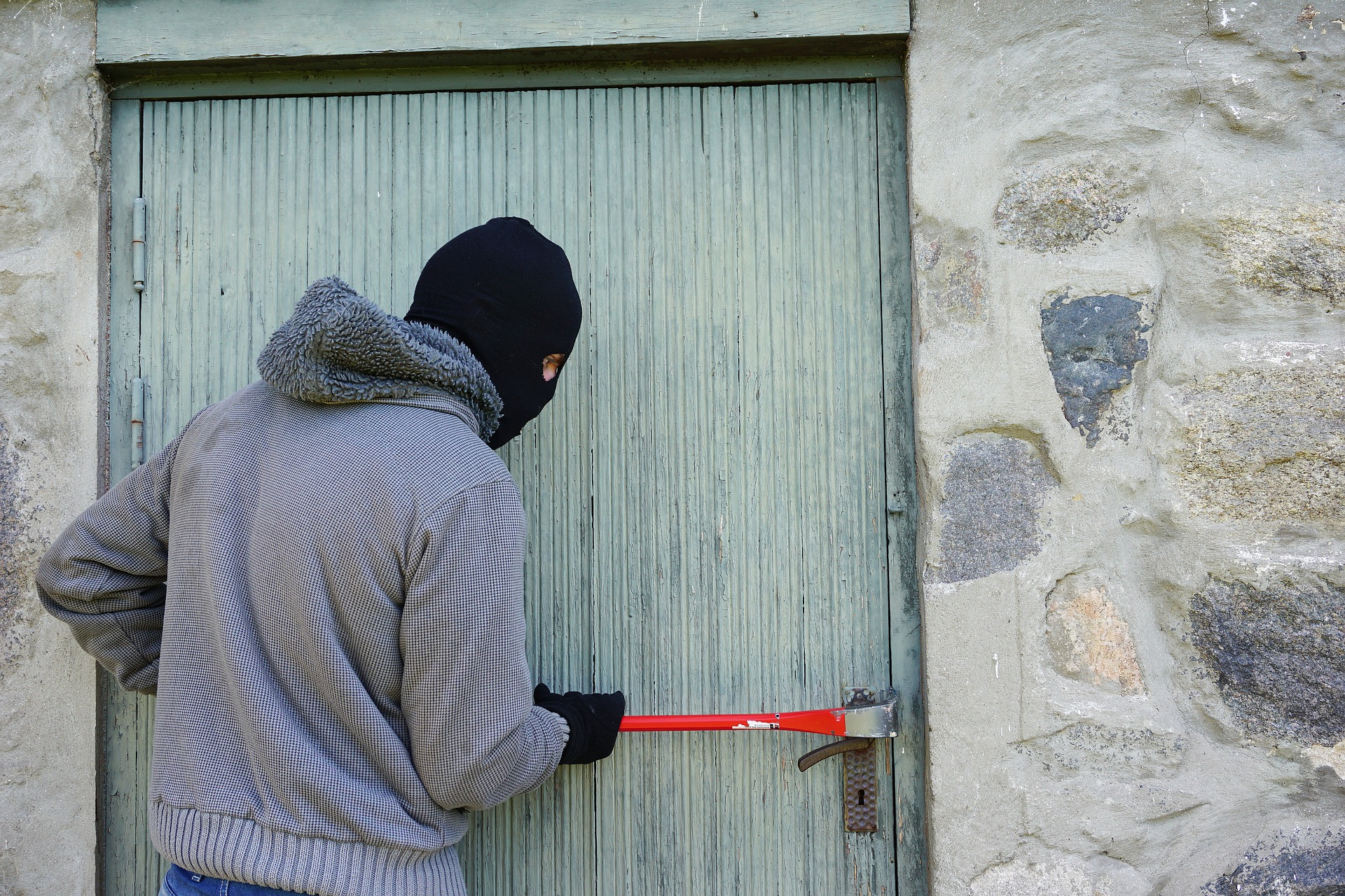 crime increase over the holidays - hooded person using crowbar to force open a door