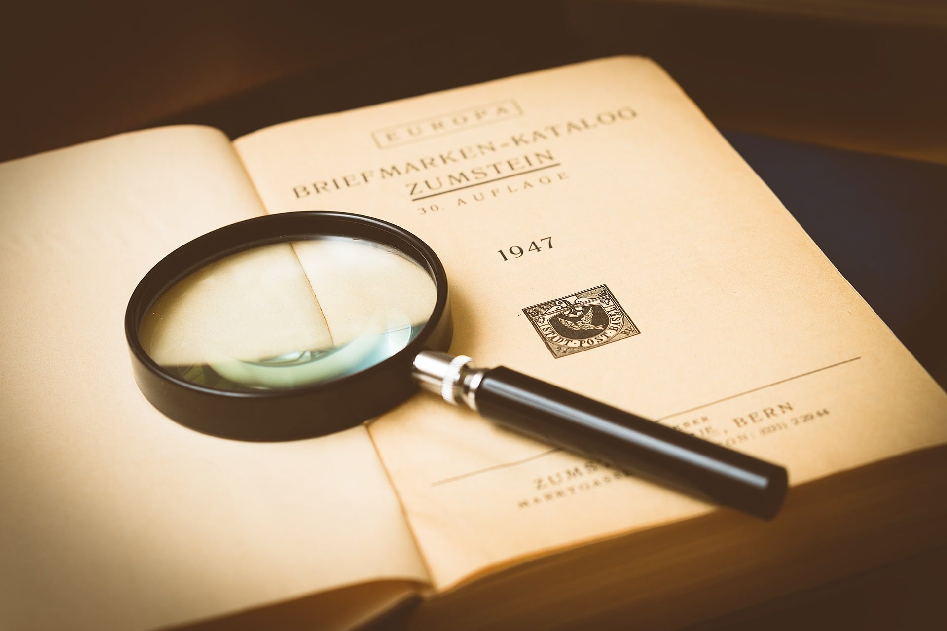 elements of a crime - magnifying glass resting on an open book